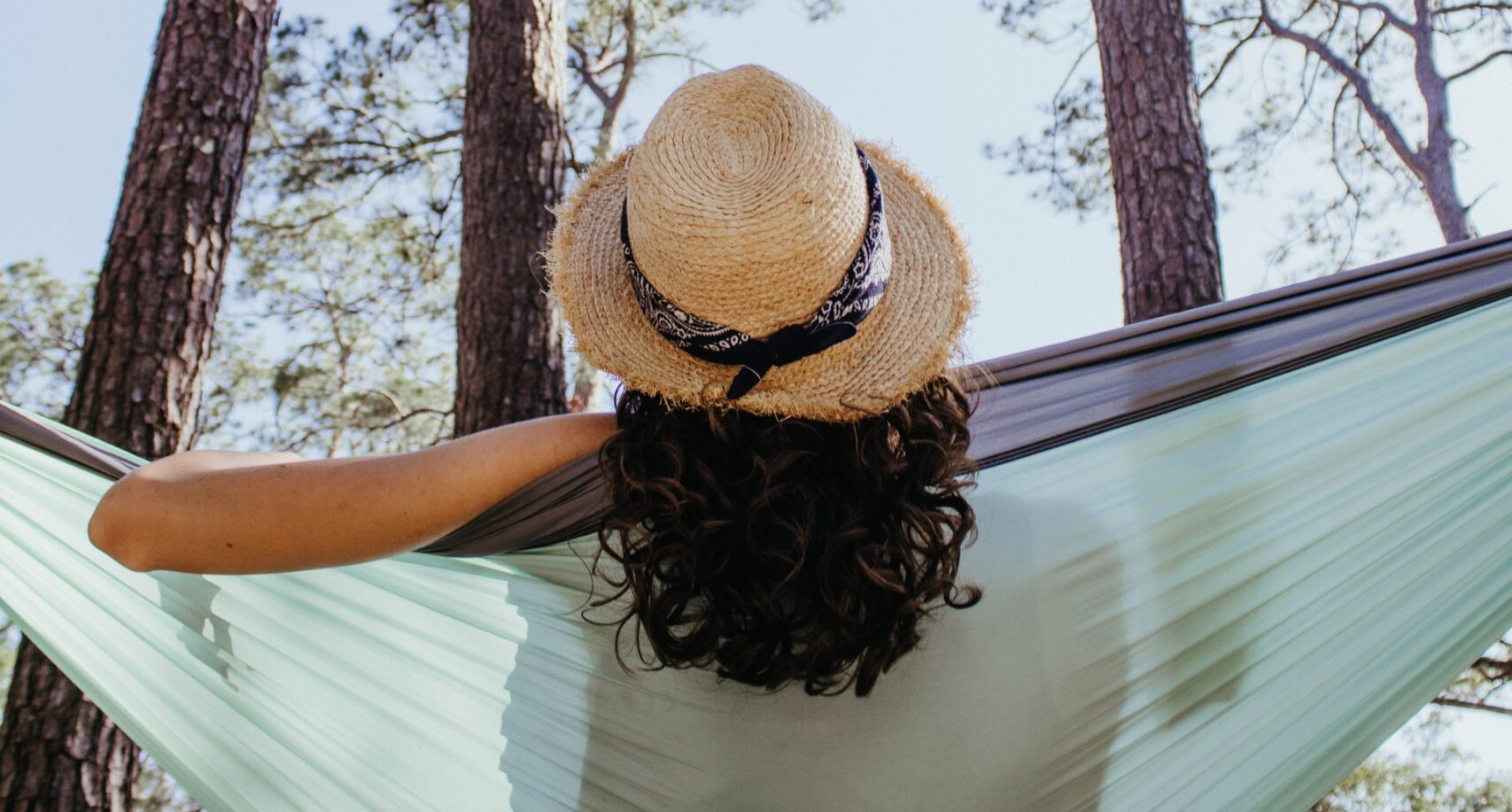 Woman with hat relaxing on hammock