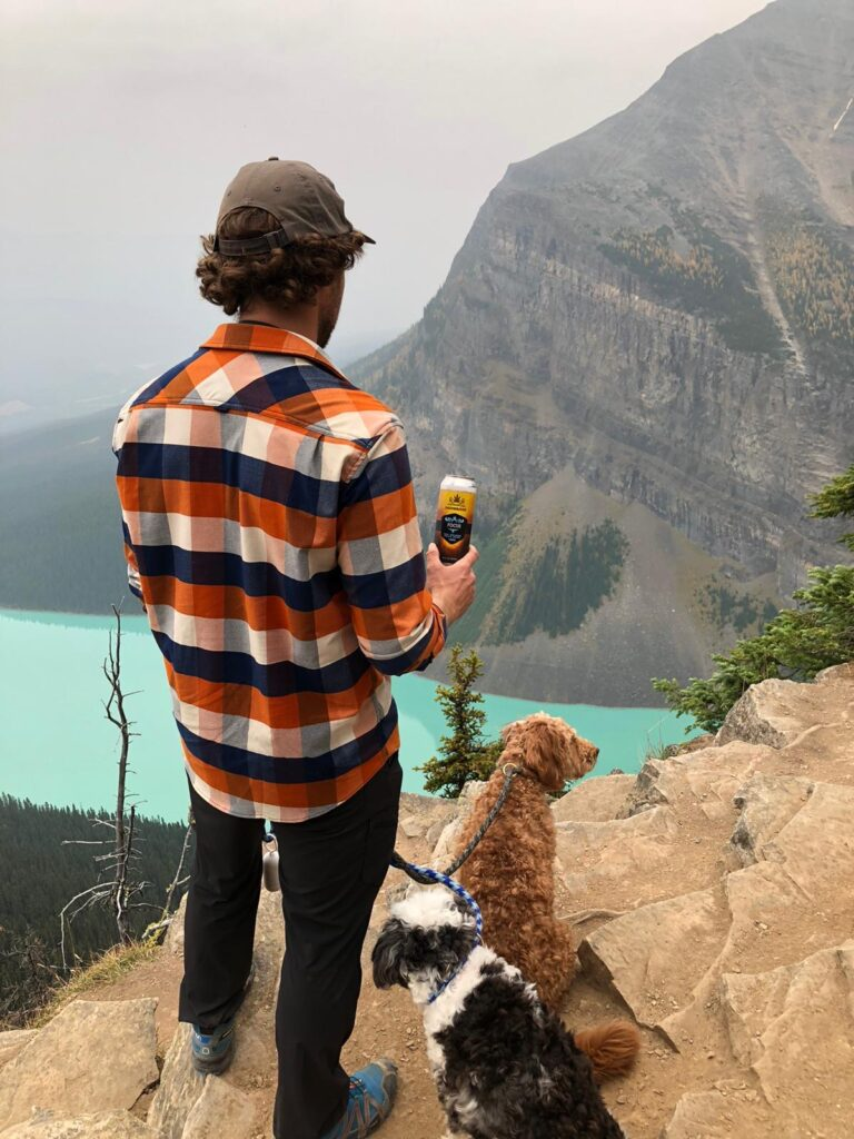 Man with hat and plaid shirt looking out over water with dog and HighBridge Faux Beer