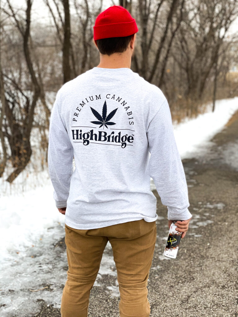 Man wearing sweatshirt with navy HighBridge logo on the back, holding a ReFrsh Seltzer