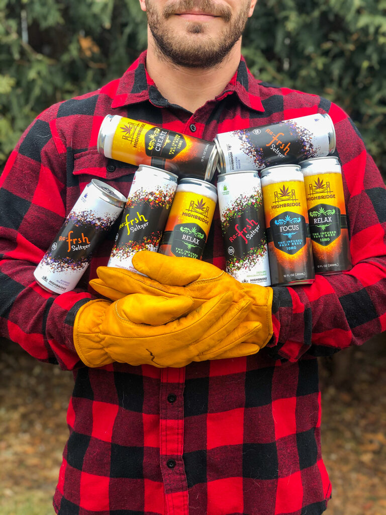 Man holding as many HighBridge cans as he can